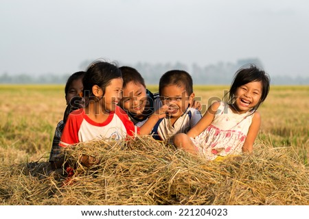 MEKONG DELTA, VIET NAM- 21 SEP 2014: Group of unidentified Asian children have fun at paddy field after harvested in sunny day, pretty, lovely face with innocent smile of kid in Mekong Delta, Vietnam - stock photo