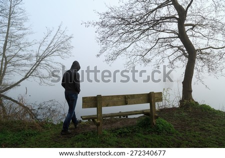 Melancholy emotions concept: sad man approaching a bench at a lake on a foggy day. - stock photo