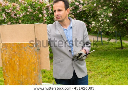 Melancholy male artist painting a masterpiece on a trestle and easel painting during an art class in a forest - stock photo