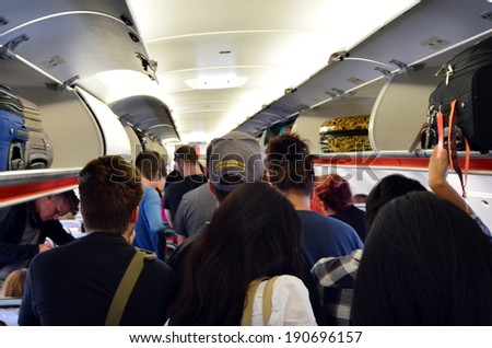 MELBOURNE - APR 10 2014:Interior of airplane with passengers get on board.According to Us Travel Association, the average age of leisure travelers is 47.5 years old. - stock photo