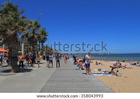 MELBOURNE AUSTRALIA - DECEMBER 29, 2015: Unidentified people visit St Kilda beach in Melbourne. St Kilda is home to many attractions such as Luna Park and St Kilda beach.  - stock photo
