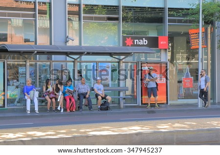 MELBOURNE AUSTRALIA - DECEMBER 5, 2015: Unidentified people wait at bus stop in Melbourne city centre. Bus is one of the key public transport in Melbourne.  - stock photo