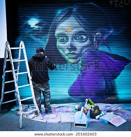 MELBOURNE, AUSTRALIA - JUNE 28 2014: Unidentified street artist at work. Melbourne's graffiti management plan recognises the importance of street art in a vibrant urban culture - stock photo