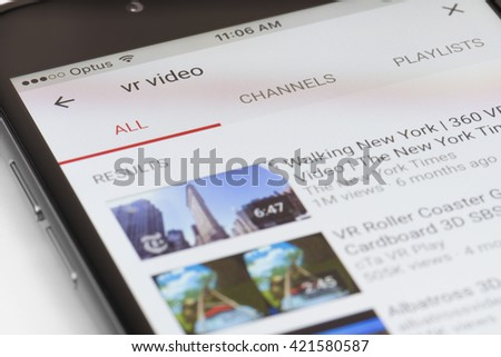 Melbourne, Australia - May 17, 2016: Close-up view of iPhone running newly updated YouTube app with a list of VR videos. This update allows users to watch videos in VR with Google Cardboard - stock photo
