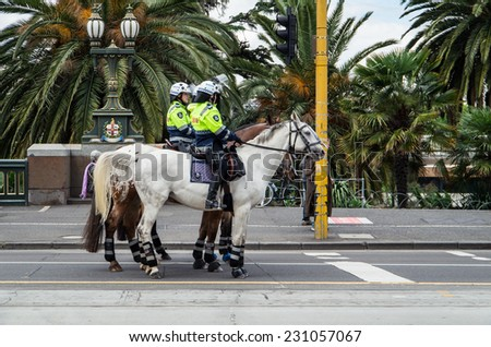 MELBOURNE, AUSTRALIA - November 16, 2014: Victoria Police mounted police officers on St Kilda Road.  Victoria Police mounted officers are often used for crowd control situation, such as protests. - stock photo