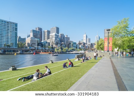 Melbourne, Australia - October 8, 2015: View of Melbourne's skyline and people sitting in lawn enjoying the sunshine in Southbank Promenade in Melbourne.  - stock photo