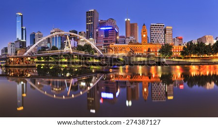 Melbourne CBD cityline at sunrise reflecting bright city illumination lights in still yarra river waters - stock photo