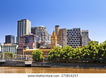 Melbourne city CBD cityline at Yarra river with greet trees and yellow river waters under blue sky - stock photo