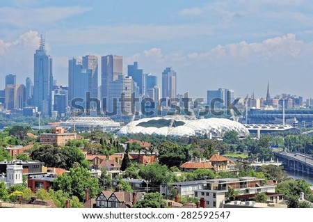 Melbourne city CBD cityscape rising over Yarra river on sunny summer day - skyscrapers, ferry terminal, train station, river line - stock photo