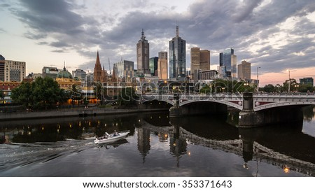 Melbourne City Skyline Reflection Cityscape, Princes Bridge from Southbank and Moving Speedboat cruise in Yarra River under Dramatic Sky at Dusk, Australia - stock photo