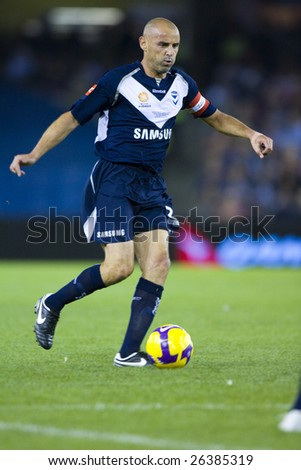 MELBOURNE - FEB 28: A-league Major Grand Final - Melbourne Victory defeat Adelaide United 1-0 on February 28, 2009 in Melbourne, Australia. Kevin Muscat controls the ball up field. - stock photo