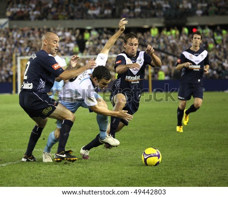 MELBOURNE - MARCH 20: Melbourne Victory captain Kevin Muscat (L) lays a heavy tackle on a Sydney FC opponent  in the  A-League grand on March 20, 2010 in  Melbourne. - stock photo