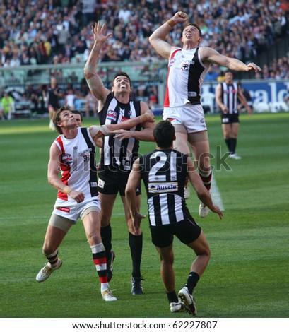 MELBOURNE - OCTOBER 2: St Kilda's Brendon Goddard leaps high over Collingwoods Darren Jolly  during  Collingwood's AFL Grand Final win at the MCG - October 2, 2010 in Melbourne, Australia - stock photo