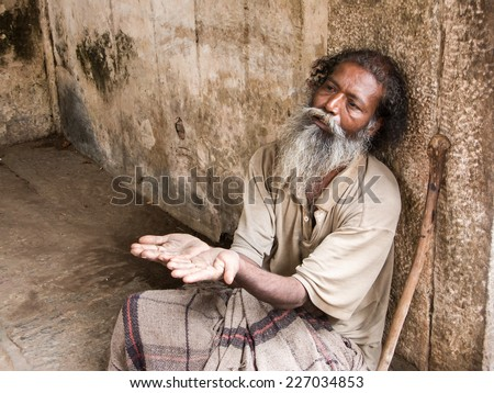MELKOTE, INDIA - MAY 9th - An old Indian beggar waits for alms on a street corner on May 9th 2008 at Melkote, India. - stock photo