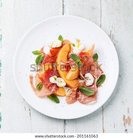 Melon and prosciutto ham salad with Mozzarella and mint leaves - stock photo