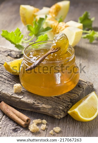 melon jam in a glass jar, the ingredients for preparation of jam on a wooden background - stock photo
