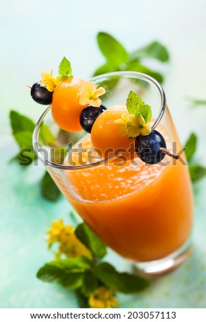 Melon smoothie with fruit skewer - stock photo