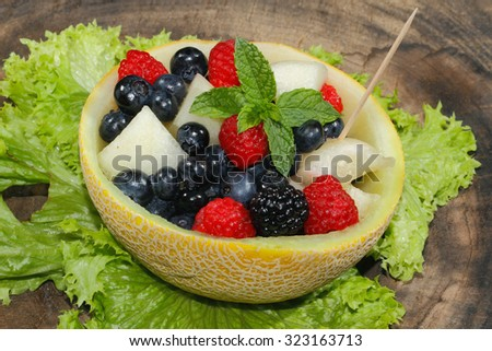 Melons bits, raspberries, blackberries and blueberries in a halved and hollowed Galia melon, garnished with mint - stock photo