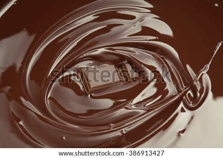 Melted chocolate swirl with chocolate bar piece/ chocolate background - stock photo