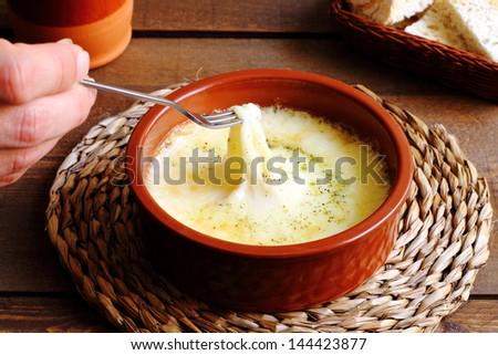 Melted provolone cheese with oregano, fondue - stock photo