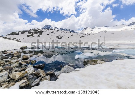 Melting glacier and the lake of clear blue water at an altitude of 2400 meters in the Alps - stock photo