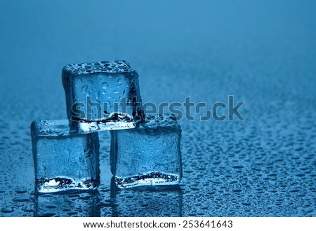 Melting ice cubes on blue background - stock photo