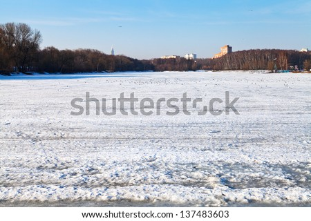 melting ice on frozen urban lake in early spring day - stock photo