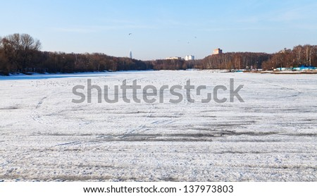 melting ice on icebound urban lake in early spring day - stock photo