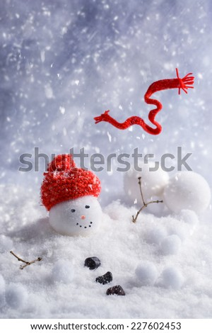 Melting snowman with red knitted scarf blowing in the wind  - stock photo