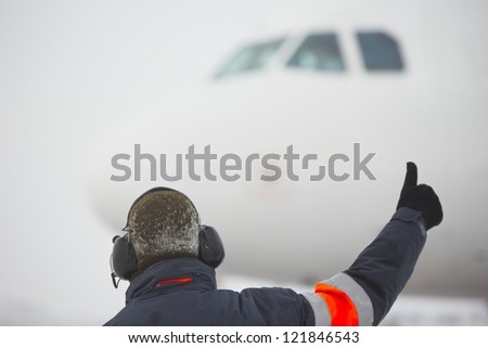 Member of ground crew is showing OK sign to pilot - selective focus - stock photo