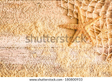Mementos of a tropical summer vacation with a starfish, fishing net and scattered golden beach sand on rustic wooden boards with copyspace for a pretty nautical background - stock photo