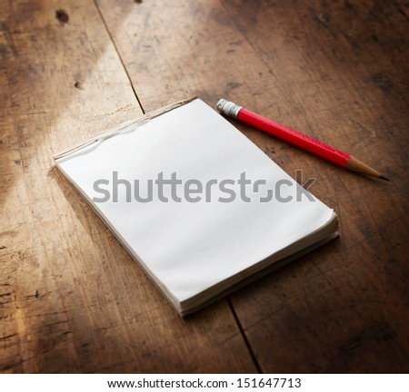 Memo pad on a well used old wooden surface with pencil. - stock photo
