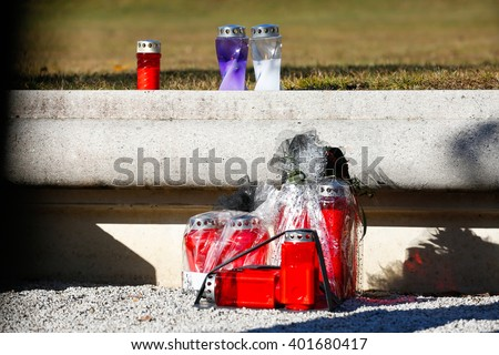 Memorial candles burning on the edge of an ashes scattering field. Death, passing, remembrance, funeral, sympathy and Day of the dead concept.   - stock photo