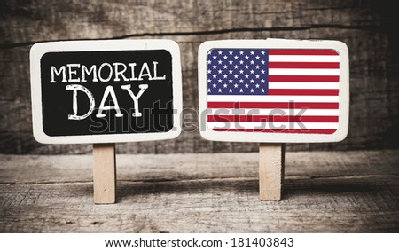 Memorial Day holiday sign written on a chalkboard with American flag on wooden background - stock photo