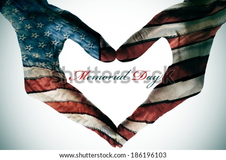 memorial day written in the blank space of a heart sign made with the hands patterned with the colors and the stars of the United States flag - stock photo
