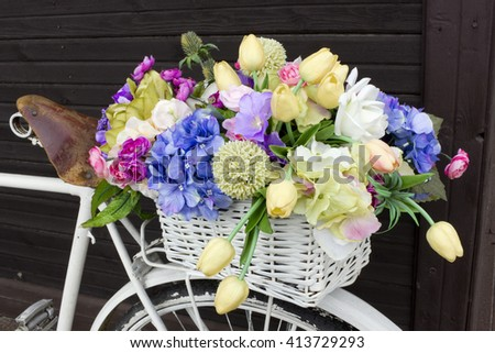Memories of the died cyclist abstract concept. Bouquet of rag and paper flowers in a white basket - stock photo