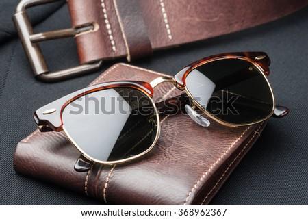 men accessories, closeup brown sunglasses  - stock photo