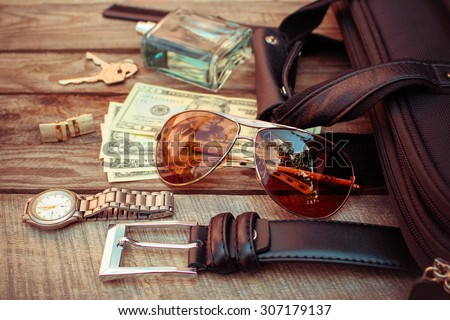 Men accessories: sunglasses,  bag, money, wrist watch, cufflinks, comb, strap, keys, perfume on the old wood background. Toned image.  - stock photo