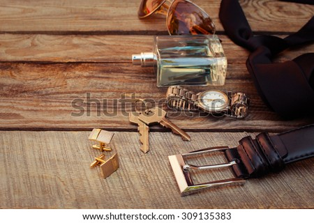 Men accessories: sunglasses, bag,  wrist watch, cufflinks, comb, strap, keys, tie, perfume on the old wood background. Toned image.  - stock photo