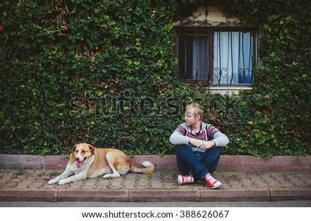 men and dog sitting near the wall with window covered with greenery - stock photo