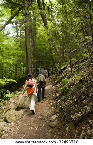 Men and Women Hikers on a Trail in Forest - stock photo
