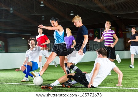 Men and women in mixed sport team playing football or soccer indoor and trying to score goal - stock photo