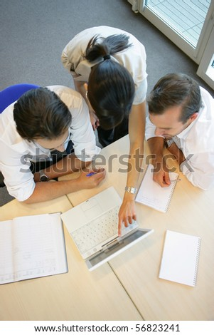 Men and women in the office to a laptop - stock photo