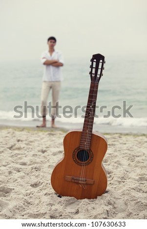 Men at the beach and guitar. - stock photo