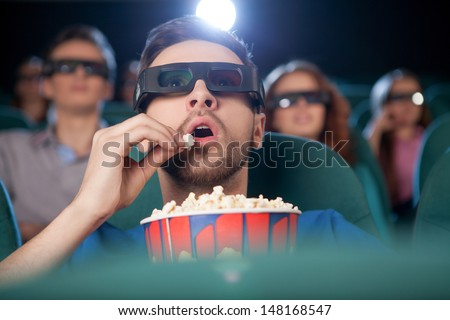 Men at the cinema. Excited young men in glasses watching movie at the cinema and eating popcorn - stock photo