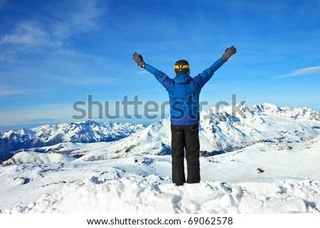 men at the top of a snowy mountain with his hands up - stock photo