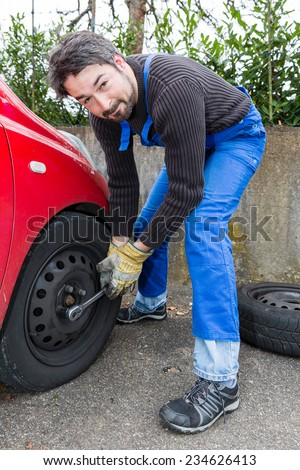 men at work - tire change with nut runner - stock photo