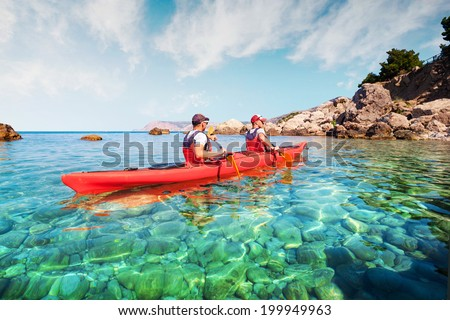 Men by sea kayaking. Traveling by kayak. Leisure activities on the water. - stock photo
