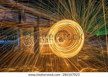 Men cast Beach Fire steel wool - stock photo
