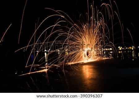 Men cast field Fire steel wool, Man and fire spin - stock photo